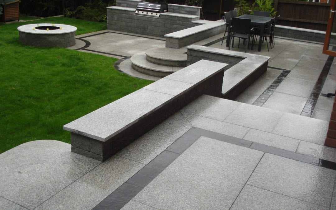 Tiered patio area in Granite with bespoke cut steps.